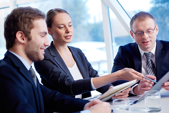 stock-photo-group-of-confident-business-partners-discussing-paper-at-meeting-130378301